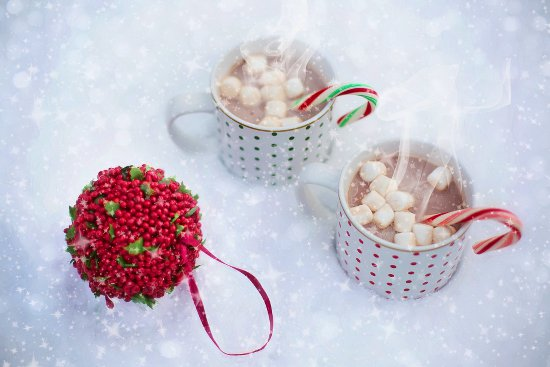 Two cups of hot cocoa sitting in the winter snow.