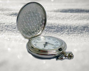 Pocket watch in the snow representing winter as the time to buy or sell.